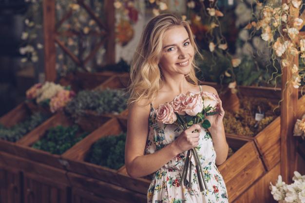 Jovem com vestido florido segurando flores rosas.